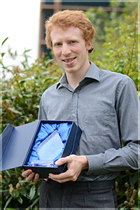 Photograph of Chris Millson holding his Blackboard Europe award.