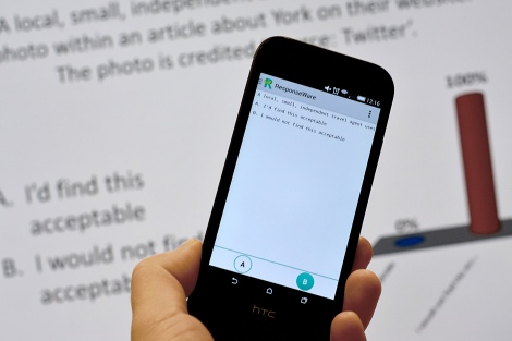 Photo of ResponseWare app on phone with TurningPoint slide in background