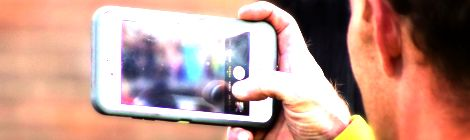Photo of someone holding a mobile phone in video capture mode