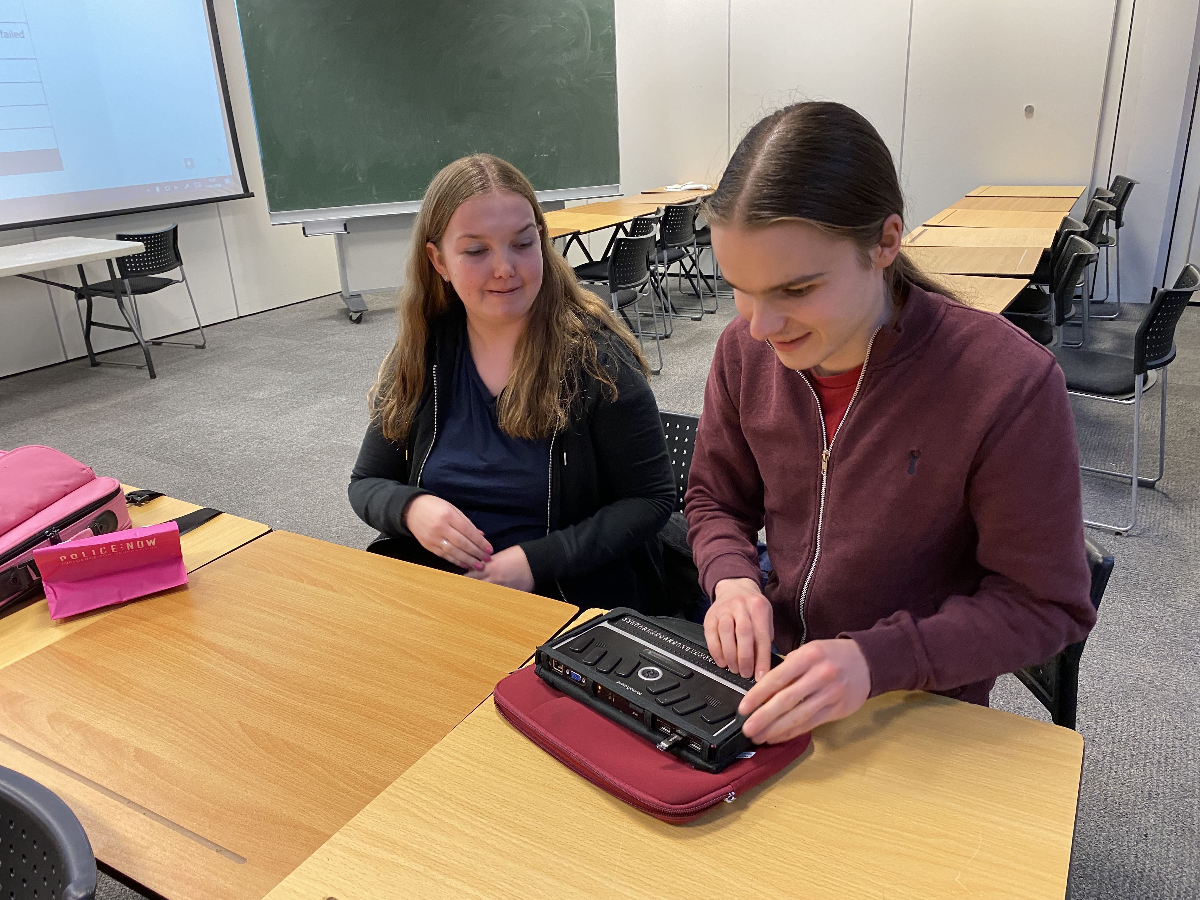 A female VI student looking on as the male VI student tries out her braille machine.